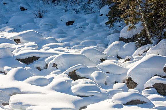 Snow covered rocks in creek.